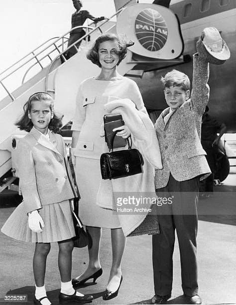 Fulllength image of American actor Lauren Bacall smiling with her children with actor Humphrey Bogart Leslie and Stephen Bogart while standing in...