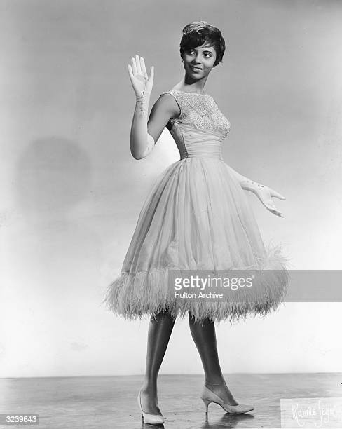 Fulllength studio portrait of singer and actor Leslie Uggams waving while wearing long white gloves and a dress trimmed with ostrich plumes