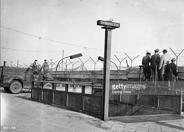 Soldiers outside the entrance to Berlin's Potsdamer Platz underground station next to a section of the Berlin Wall