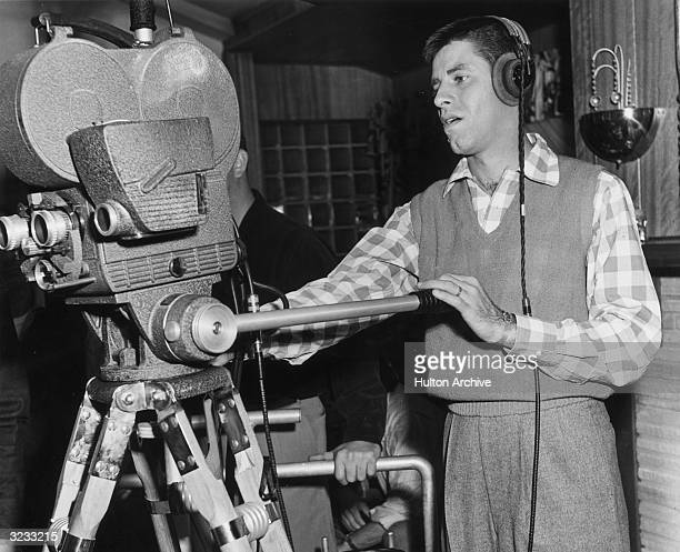 American actor comedian and director Jerry Lewis wearing headphones and standing behind a movie camera