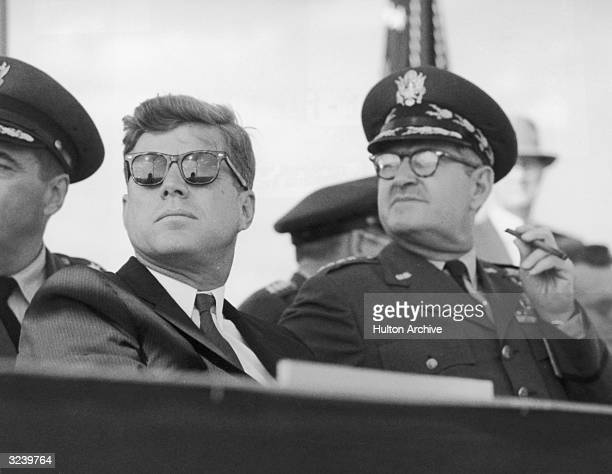 American president John F Kennedy wearing dark sunglasses sits next to US Air Force Chief of Staff Curtis LeMay