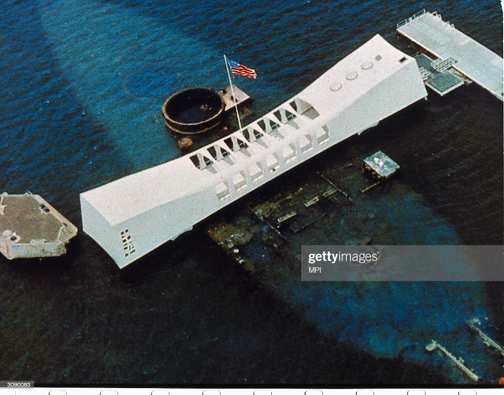 An aerial view of the USS Arizona National Memorial, which spans the sunken hull of the battleship in Pearl Harbor, Oahu, Hawaii, and commemorates the site where the Japanese attacked on December 8, 1941 bringing America into World War II, and as a memorial to all the military personnel killed that day.