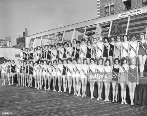 Group portrait of the fifty Miss America contestants wearing swimsuits and sashes and posing on the boardwalk in Atlantic City New Jersey