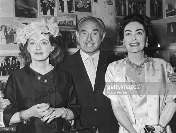 Left to right American actor Bette Davis Canadian movie producer Jack L Warner and American actor Joan Crawford pose for a photo Both actors starred...