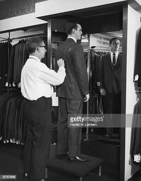 A tailor draws on the back of a man's suit with chalk taking measurements for alterations in a men's garment store