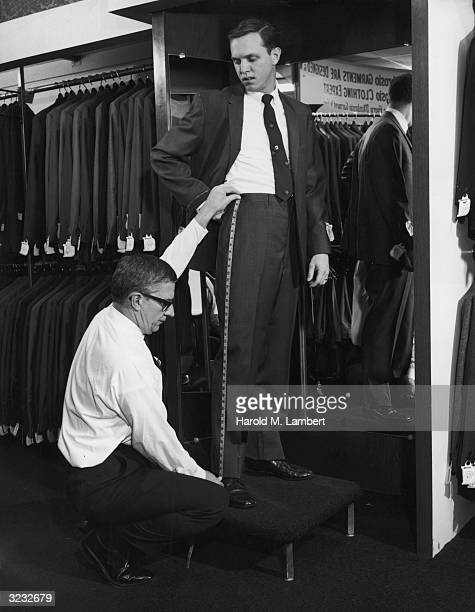 A tailor uses a tape measure to measure a man's pants for alterations in a men's garment store