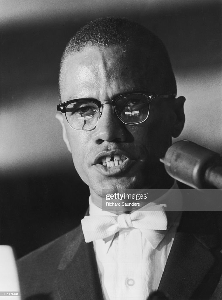 Black nationalist and Muslim leader Malcolm X speaking into a microphone
