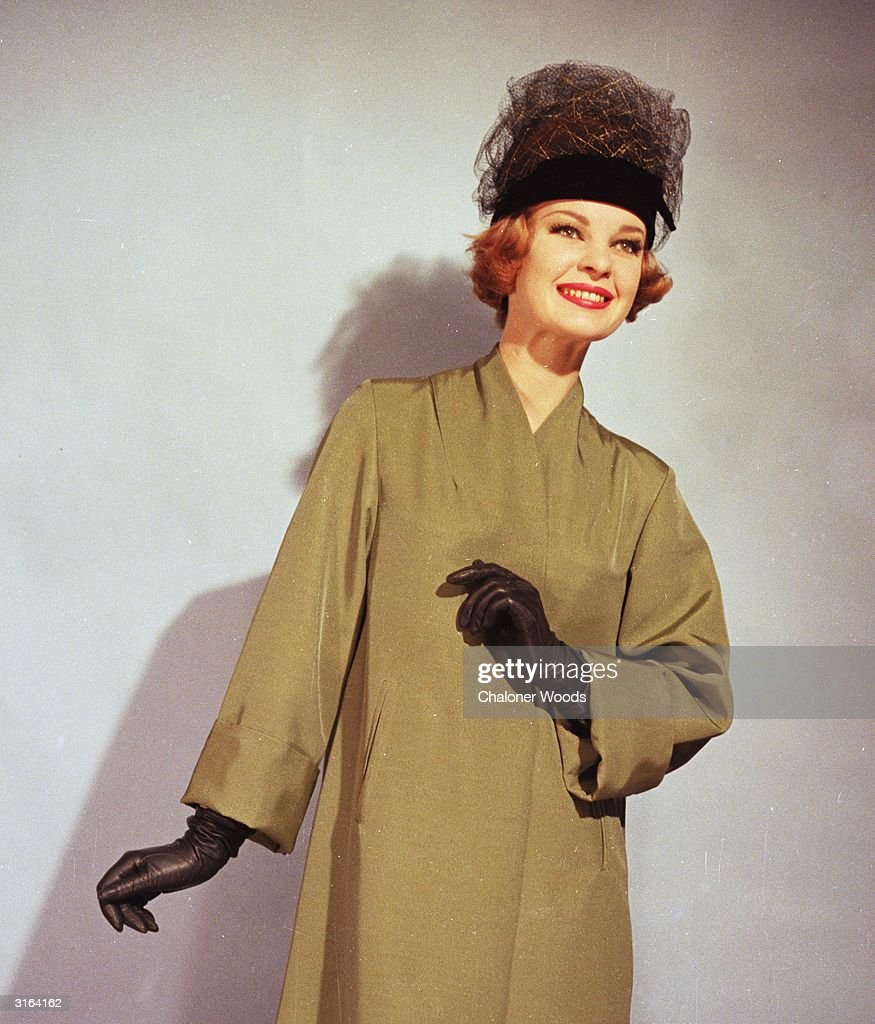 Khaki green duster coat. Set-in sleeves are bracelet length and have wide cuffs. Worn with black gloves and a black tulle hat.