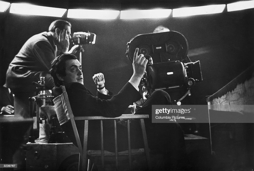 American film director Stanley Kubrick (1928 - 1999) sits near a movie camera on the set of his film, 'Dr. Strangelove or: How I Learned to Stop Worrying and Love the Bomb,' Shepperton Studios, England.