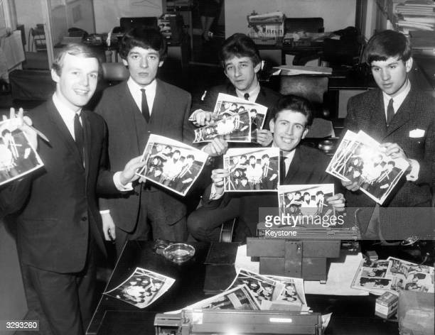 British pop group The Hollies holding publicity photographs of themselves