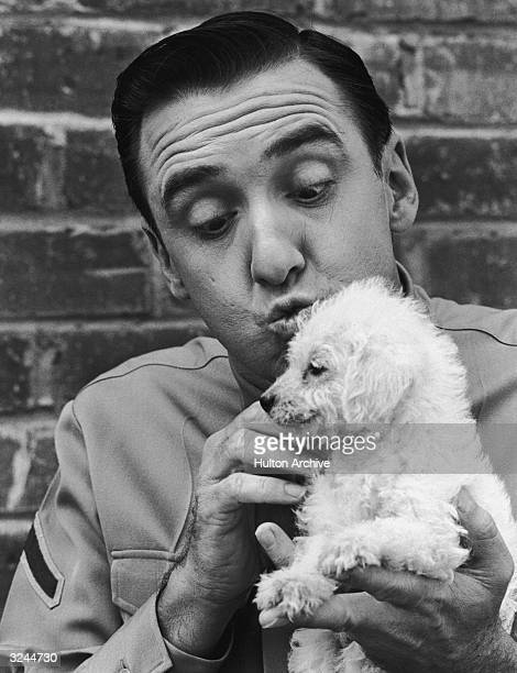 Headshot of American actor and singer Jim Nabors wearing a military uniform and cuddling a poodle from his television series 'Gomer Pyle USMC'