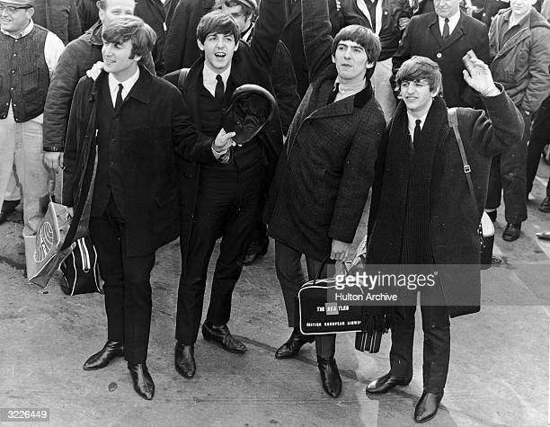 The British rock group The Beatles wave to a crowd at an airport as they arrive in the US for concerts and television appearances