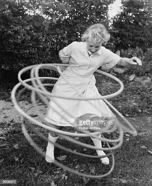 A blonde girl in a lightcolored blouse and a skirt twirls eight hula hoops simultaneously while standing outdoors in a yard