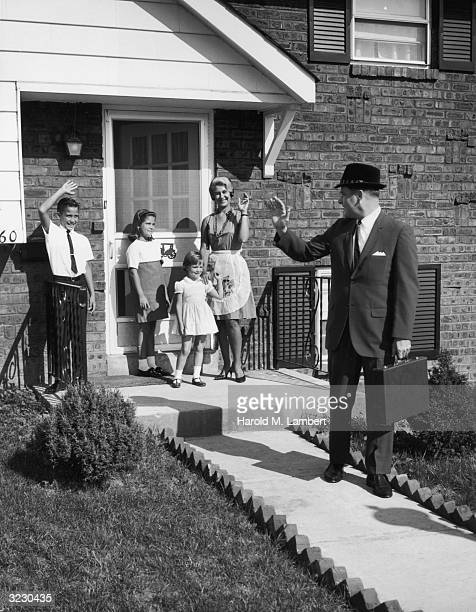 A businessman waves goodbye to his family as he walks with a briefcase down the walkway of his house His wife and their three children stand at the...
