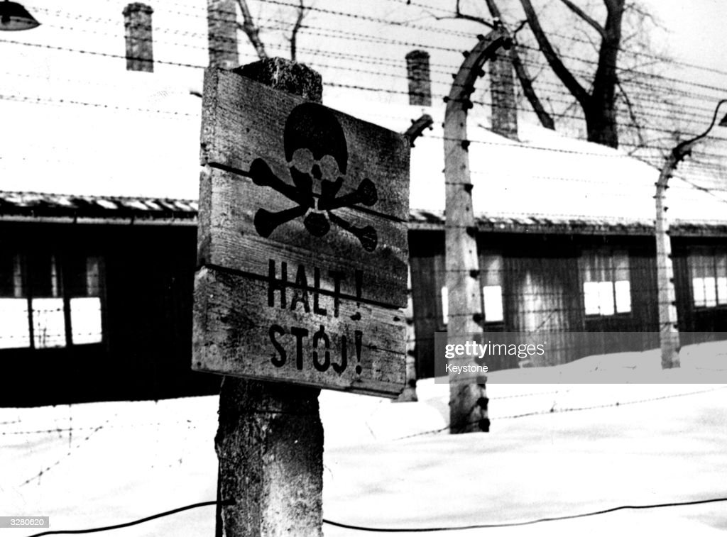 A concentration camp, possibly Auschwitz, in the snow. A sign with a death's head warns passers-by to stay away.