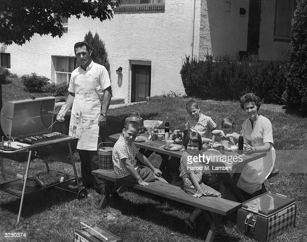 A family sits outdoors at a picnic table as the father grills hot dogs on their back yard barbecue A cooler sits on the ground The father wears an...