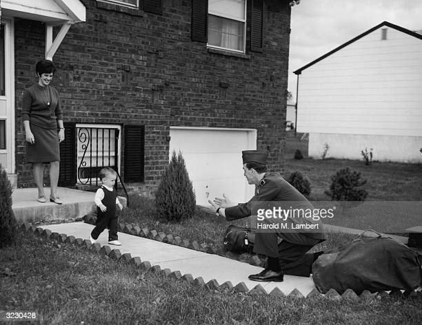 A father in his military uniform crouches with his arms outstretched as his infant son runs toward him on the walkway in front of his house The...