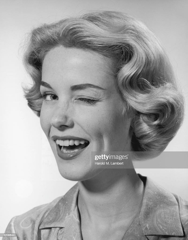 A headshot of a blonde woman winking.