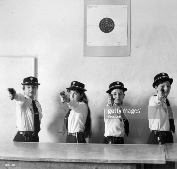 A line of female police officers take aim during a target practice session