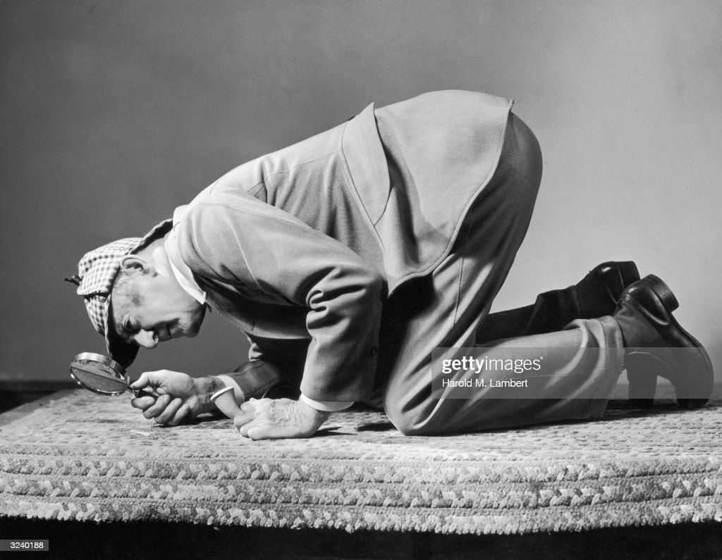 A man wearing a Sherlock Holmes costume kneels on his hands and knees to inspect a carpet with a magnifying glass while holding a meerschaum pipe.