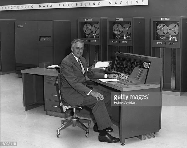 A portrait of IBM CEO Thomas J Watson Jr seated in front of an IBM data processor 702