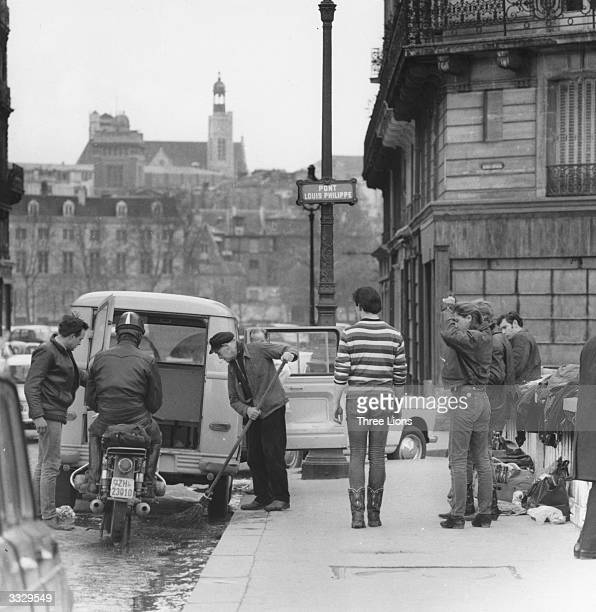 A streetsweeper traffic and passersby on the Pont Louis Philippe in Paris
