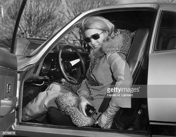 A woman smiles as she sits in the driver's seat of her car buckling her seatbelt with the door open She wears rectangular sunglasses and a furtrimmed...