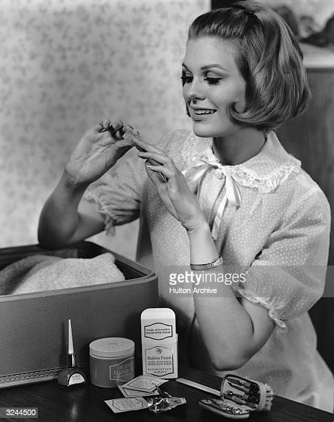 A woman wearing a night gown removes nail polish from her fingernails with Dorothy Gray Nail Enamel Remover Pads A manicure kit and nail polish rest...