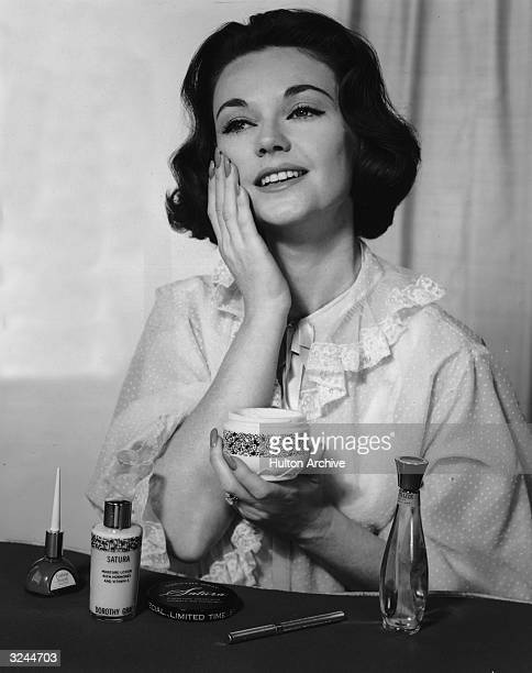 A woman wearing a night gown smiles as she applies Satura moisturizing lotion and cold cream to her face at a boudoir