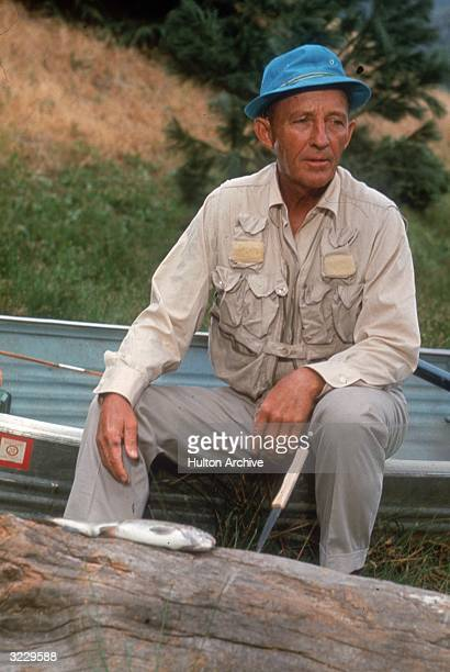 American actor and singer Bing Crosby sits outdoors on the edge of an aluminum boat in front of a log with a fish and a knife sticking into it Crosby...