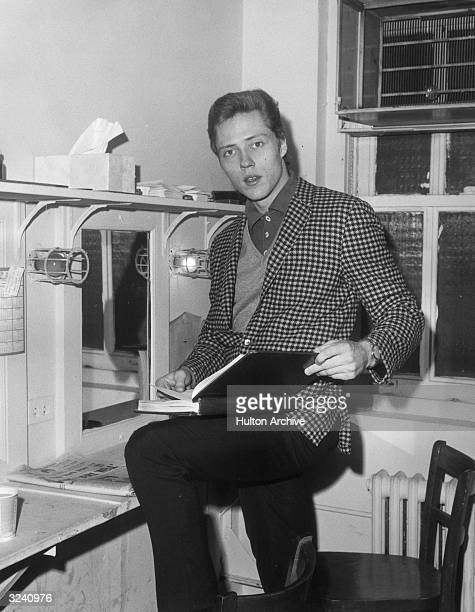 American actor Christopher Walken resting his foot on a chair while examining a script in a dressing room Walken wears a checkered jacket