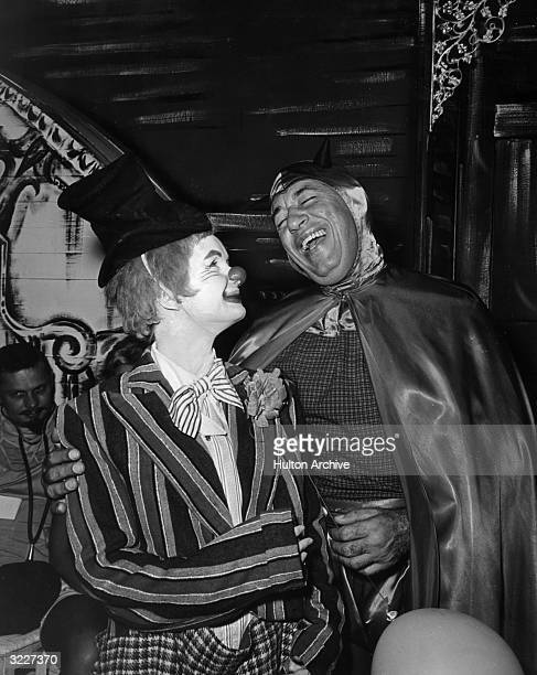 American actor Debbie Reynolds dressed in clown makeup laughs with American jazz bandleader Louis Prima dressed as the devil at a party held by men's...