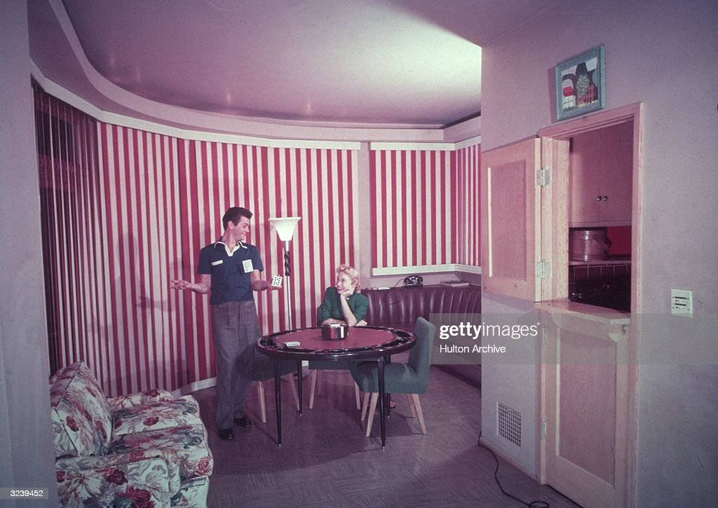 American actor Tony Curtis holds up a playing card while his wife, actor Janet Leigh, sits at a poker table in a room with red-and-white striped walls.