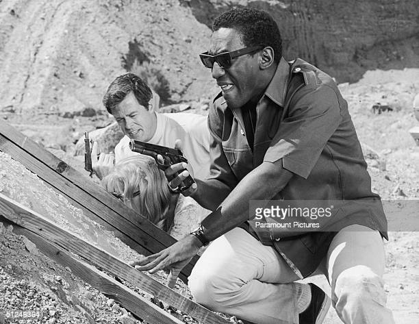Circa 1965 American actors Robert Culp left and Bill Cosby hold guns and crouch behind a mound of dirt in a still from the television series 'I Spy'...