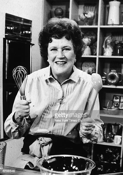 American chef Julia Child stands in front of a countertop holding a whisk and a ladle by a mixing bowl possibly on the set of her television series...