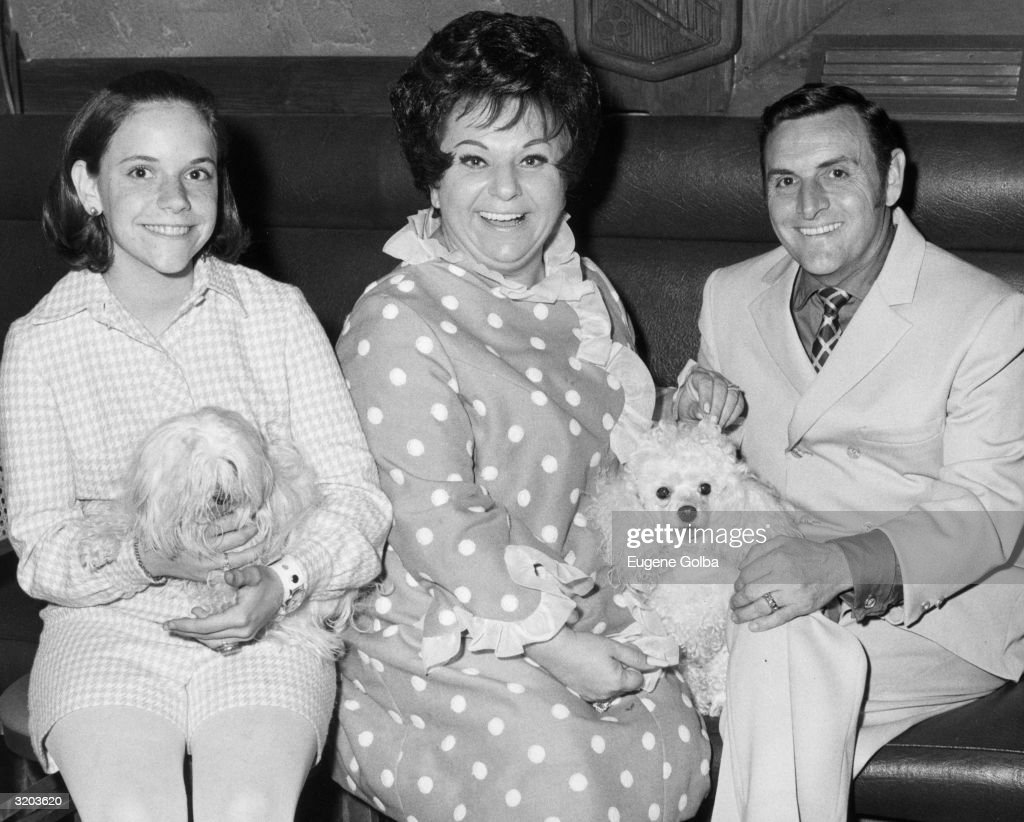 American comedian Totie Fields (C) sits with her husband, George, their daughter, Debbie, and their two dogs, 'Mike Douglas' (L) and 'Bubbles,' Springfield, USA. She wears a polka-dot dress.