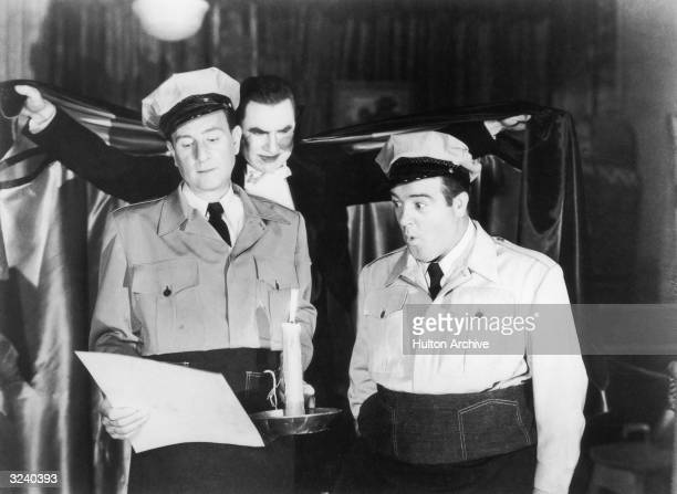 American comedians Bud Abbott and Lou Costello dressed as delivery men read a sheet of paper by candlelight while Hungarianborn actor Bela Lugosi...