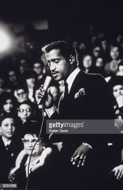 American dancer vocalist and actor Sammy Davis Jnr sings into a microphone and holds a cigarette while performing in the audience of 'The Merv...