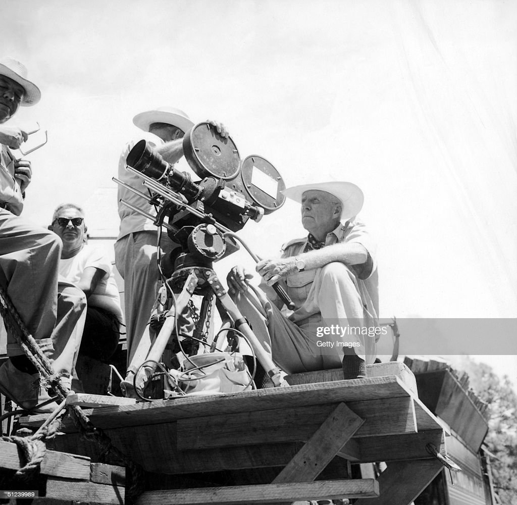 Circa 1965, American director Howard Hawks (1896 - 1977) sits on a camera mount on the set of a film, 1960s.