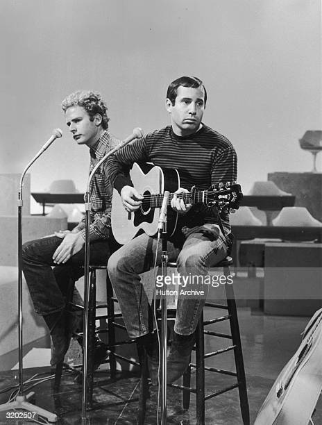 American folk rock duo Simon and Garfunkel performing on a studio sound stage during a rehearsal Garfunkel slaps his leg while Simon plays a guitar
