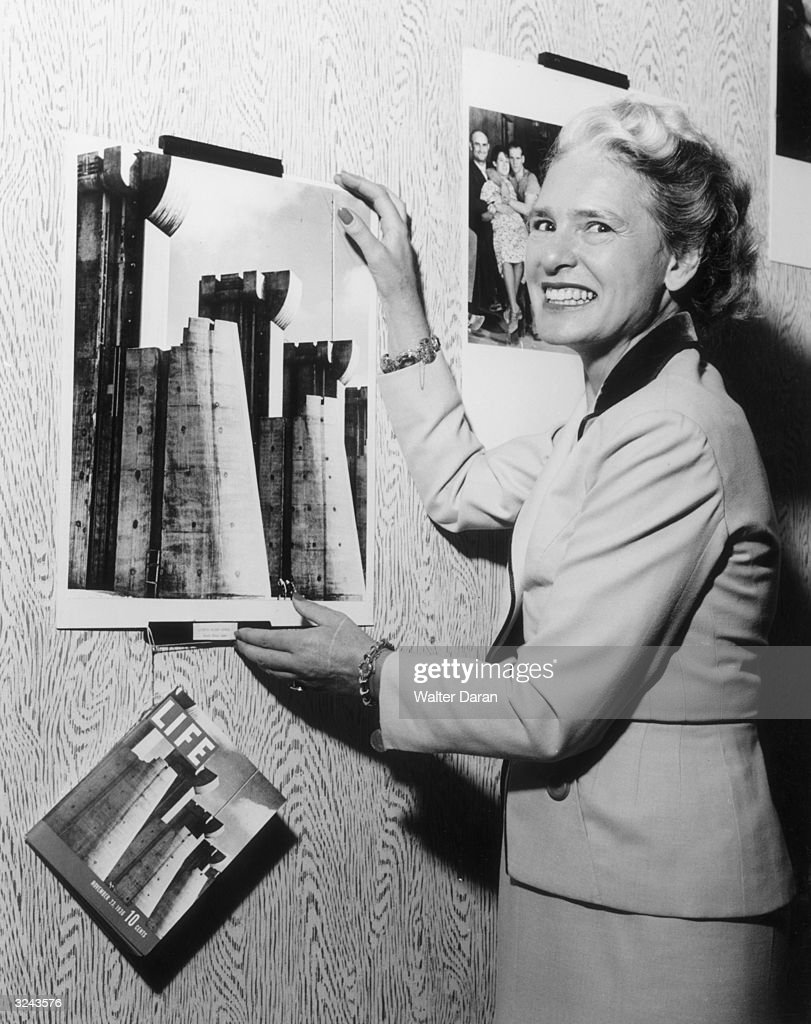 American photojournalist Margaret Bourke-White (1906 - 1971) showing a print of the photograph she took for the first cover of 'Life' magazine.