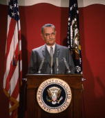 American statesman Lyndon Baines Johnson the 36th President of the United States of America making an address at a podium flanked by two flags
