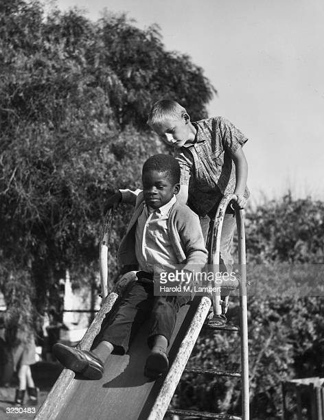 An AfricanAmerican boy sits at the top of a playground slide as a Caucasian boy stands behind him giving him a push