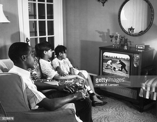 An AfricanAmerican family sits in their living room watching a baseball game on television The mother holds their daughter on her lap