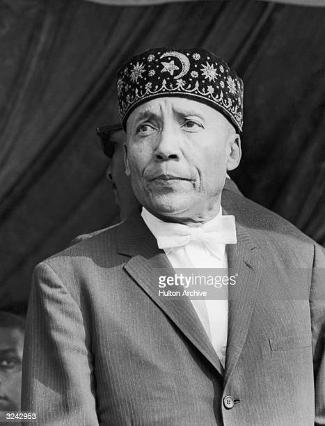 Headshot of black Muslim leader Elijah Muhammad wearing a fez with a pinstriped jacket and a bow tie