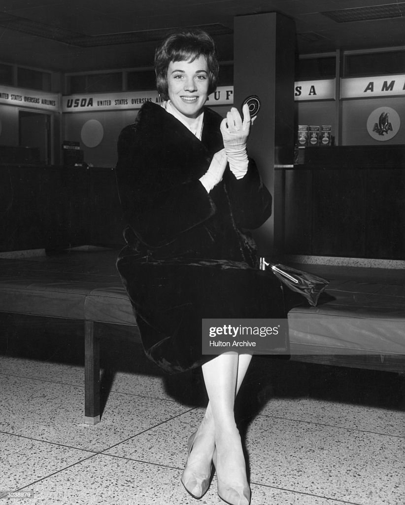 British actor and singer Julie Andrews holds a compact while sitting on a bench at the airport, New York City.