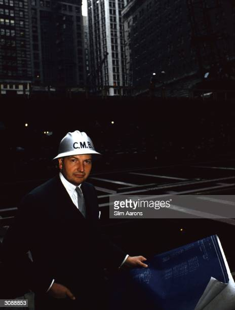 Financier David Rockefeller wears a hard hat as he stands surrounded by girders in the excavation for the Chase Manhattan Plaza in the Wall Street...