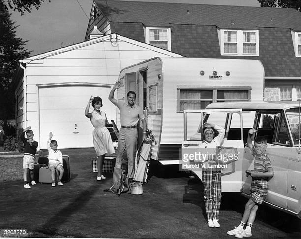 Fulllength image of a family waving from their driveway while preparing for a camping trip