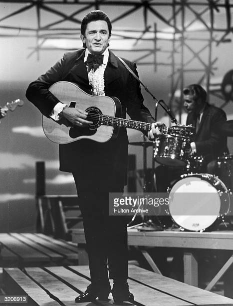 Fulllength image of American country singer and musician Johnny Cash wearing a tuxedo performing with a guitar on stage during a television appearance