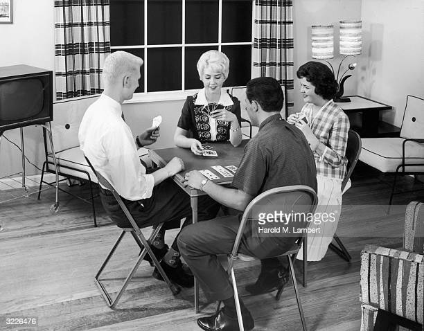 Fulllength image of two couples sitting in a living room playing a game of cards at a table with folding metal chairs